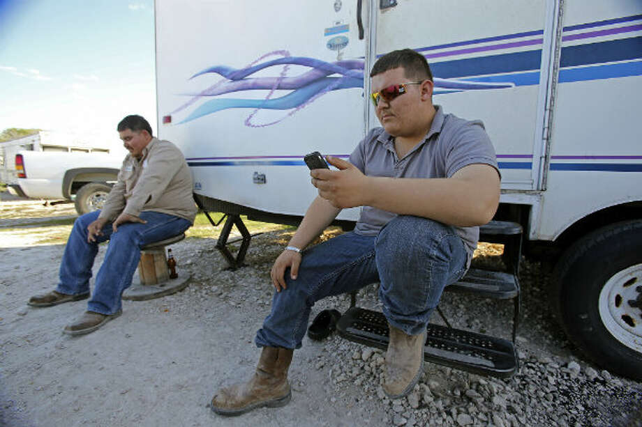 Cesar Garcia uses his cell phone after work with roommate Andres Cadena, relaxing alongside their trailer at Lonesome Creek RV Resort near Kenedy, Texas.