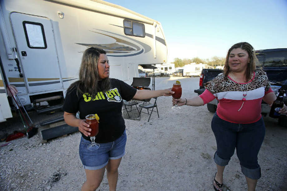 Virginia Terrazas (left) hands a Bloody Mary beverage to her sister-in-law Dulce Terrazas as they unwind and barbecue outside at the Lonesome Creek RV Resort near Kenedy, Texas.