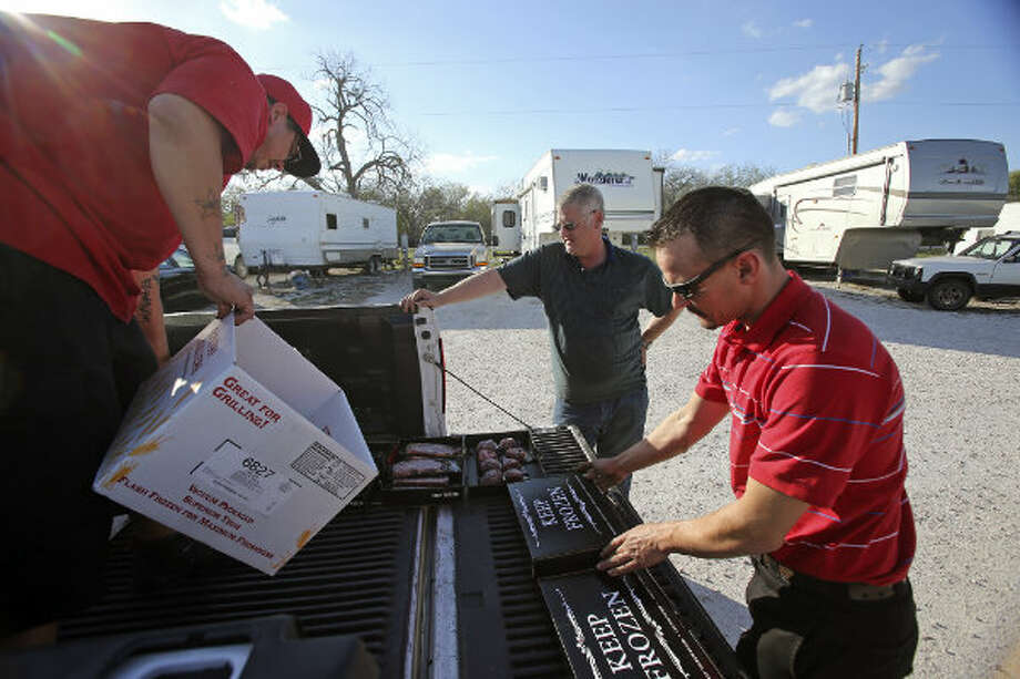 Doug Boozer buys some steaks from vendors Mike Cowan and Josh Green at Lonesome Creek RV Resort near Kenedy, Texas.