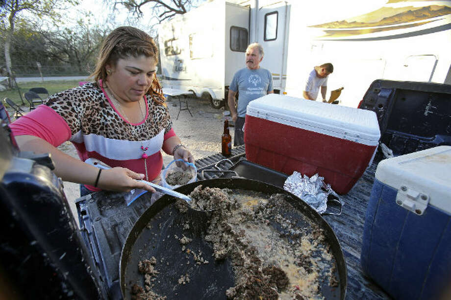 Dulce Terrazas salvages the remainder of lunch served to her crew during the day, as Andres Islas (center) and her brother Angel Terrazas unwind at Lonesome Creek RV Resort near Kenedy, Texas.