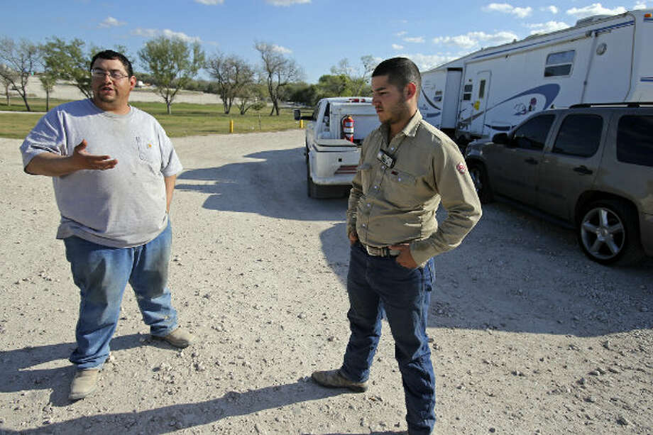 Cousins Victor Alaniz (left) and Joe Alaniz explain their economic choices in taking jobs away from home, as they return in the evening to the Lonesome Creek RV Resort near Kenedy, Texas.