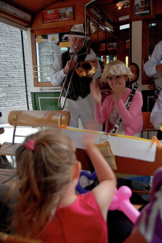 A young rider aboard the sightseeing Christchurch Tram shares her enthusiasm for the Dixieland jazz band aboard, in this 2009 photo.