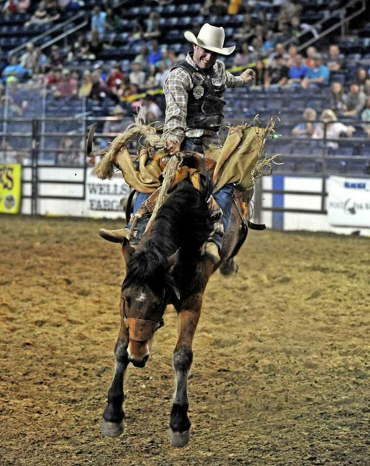 Will Smith participates in the bronco riding event at the YMBL Rodeo at the Southeast Texas State Fair on Friday, March 22, 2013. Photo taken: Randy Edwards/The Enterprise Photo: Randy Edwards