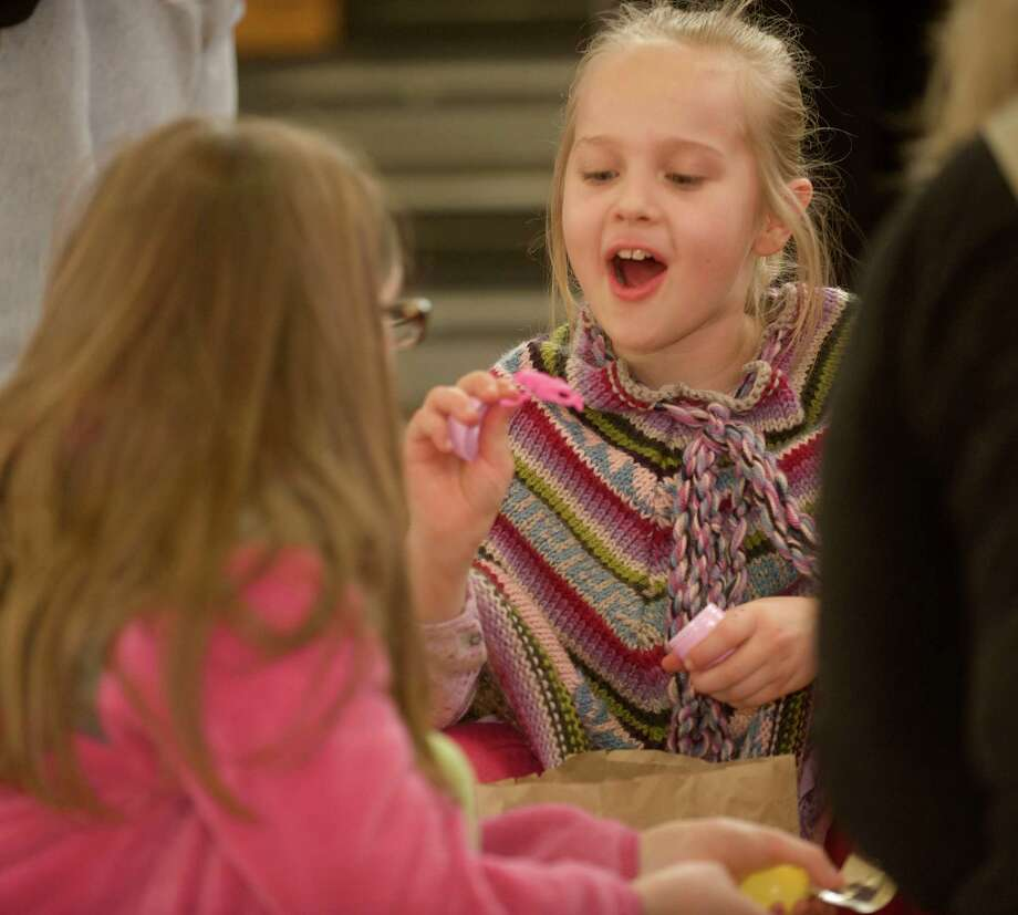 Kaelyn Chabinsky, 8 (right), of Bethel, shows a rubber frog she found in one of her Easter eggs to Olivia Landau, 8, of Danbury at the annual Bethel Conn. Easter Egg Hunt held at the Municipal Center Gym. Children from 2 years old through fourth grade participated in the hunt for 4,000 Easter eggs. Landau's grandparents are from Bethel, Saturday, March 23, 2013. Photo: H John Voorhees III / The News-Times Freelance