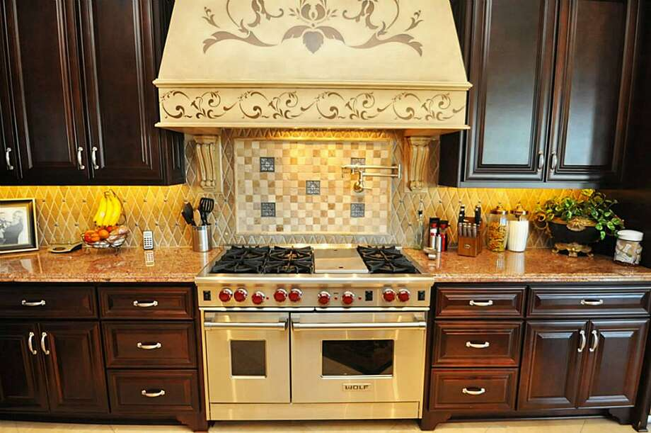 WELL APPOINTED WOLF RANGE WITH CUSTOM STENCILED HOOD Photo: Prudential Anderson Properties