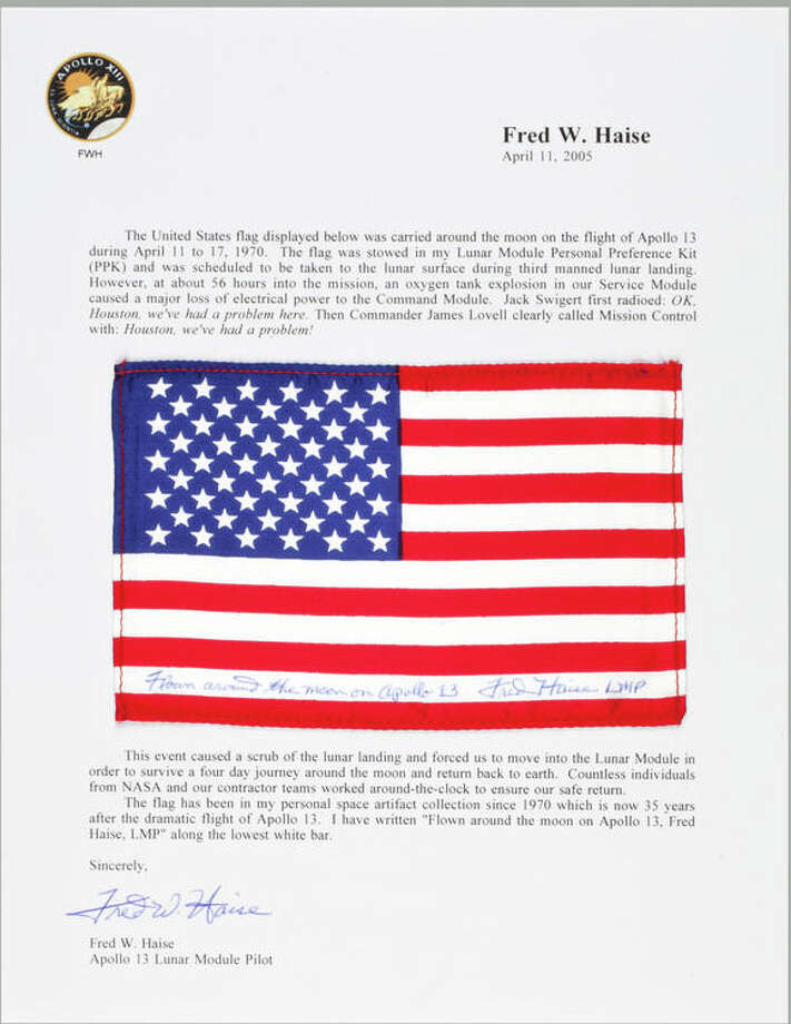 Flown United States flag, made from silk, 4 by 6 inches, inscribed on the lowest white bar: Flown around the moon on Apollo 13, Fred Haise, LMP. Displayed between paragraphs on a Typed Letter Signed by FRED HAISE.