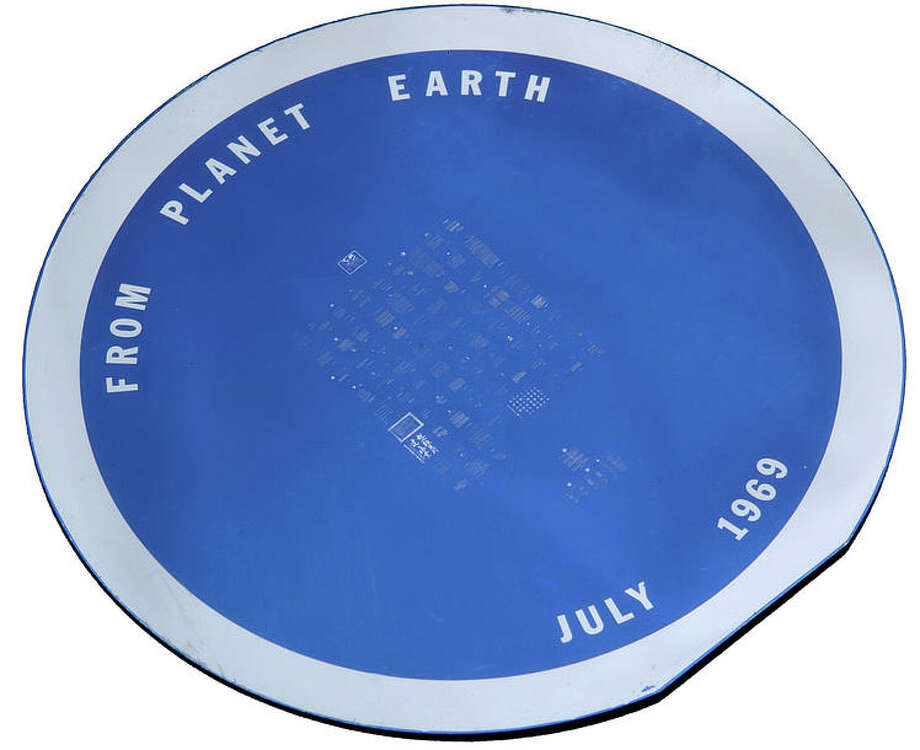A circular silicon disc, manufactured by the Semi-Conductor Division of Sprague Electric Company of North Adams, Massachusetts. 1½ inches diameter but with one flattened edge, wafer-thin, one side coated in blueish-purple coating, etched lettering From Planet Earth ... July 1969 visible to the naked eye, and an array of microscopic etching, the reverse gray-colored.