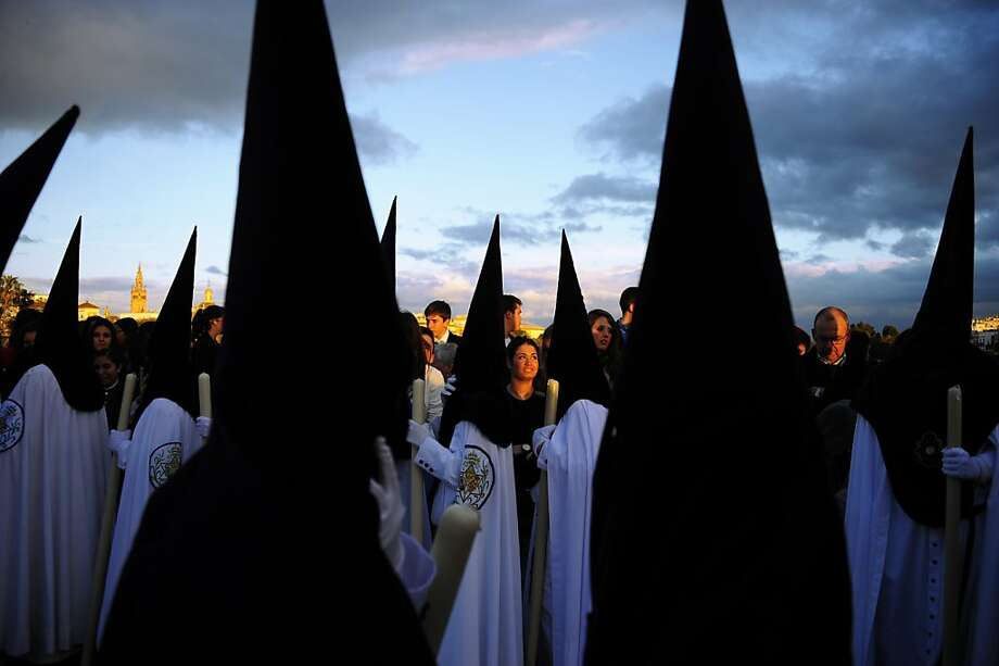 """Pointy headed penitentswait before the procession of the """"La Estrella"""" brotherhood during Holy Week in Sevilla, Spain. Christian believers around the world are marking the Holy Week of Easter. Photo: Cristina Quicler, AFP/Getty Images"""