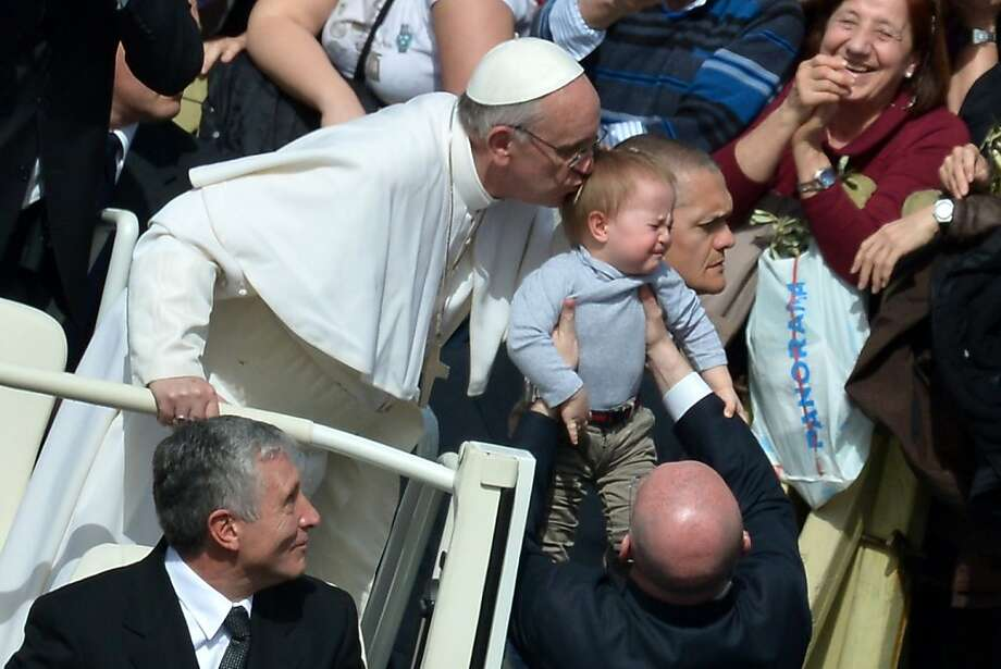 Buss stop: Pope Francis leans over to kiss a grimacing baby at the end of a Palm Sunday Mass in St. Peter's Square. Photo: Gabriel Bouys, AFP/Getty Images