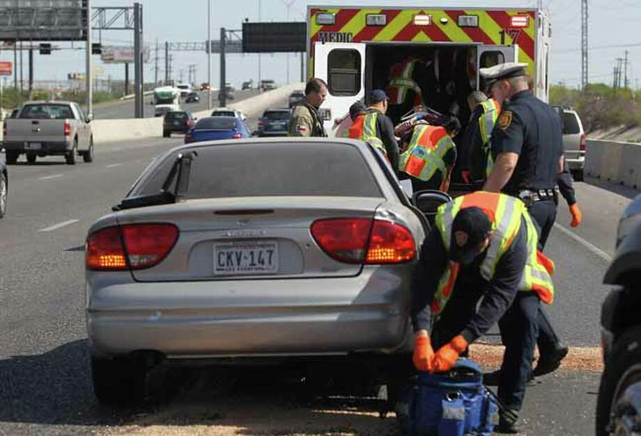 San Antonio EMS paramedics prepare to transport an accident victim (upper right, background) from the scene of a two car collision Monday March 25, 2013 on northbound U.S. Highway 281 at Jones Maltberger. An officer at the scene said an elderly couple was being transported to an area hospital with non-life threateing injuries as a precaution. The accident took place about 10:30 a.m. and backed up traffic in the area for almost an hour. Photo: JOHN DAVENPORT, SAN ANTONIO EXPRESS-NEWS / ©San Antonio Express-News/Photo may be sold to the public