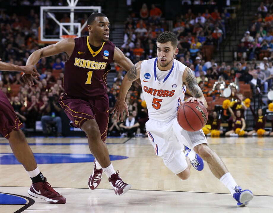 AUSTIN, TX - MARCH 24:  Scottie Wilbekin #5 of the Florida Gators drives against Andre Hollins #1 of the Minnesota Golden Gophers in the seocnd half during the third round of the 2013 NCAA Men's Basketball Tournament at The Frank Erwin Center on March 24, 2013 in Austin, Texas. Photo: Stephen Dunn, Getty Images / 2013 Getty Images