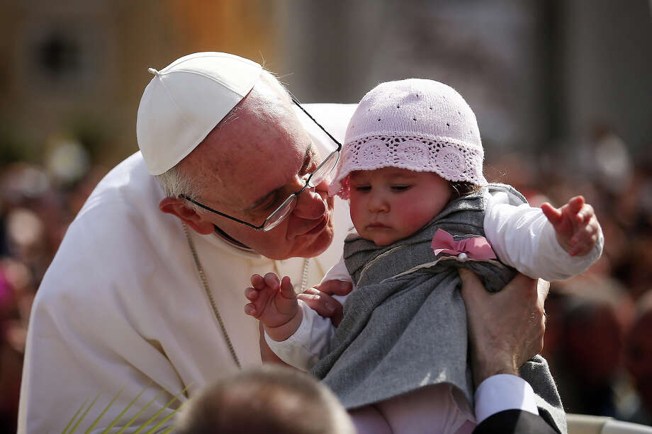 Pope Francis kisses 8-month-old Victoria Maria Marino from Sicily after delivering his blessing to the palms and to the faithful gathered in St. Peter's Square during Palm Sunday Mass on March 24, 2013 in Vatican City. Photo: Dan Kitwood, Getty Images / 2013 Getty Images