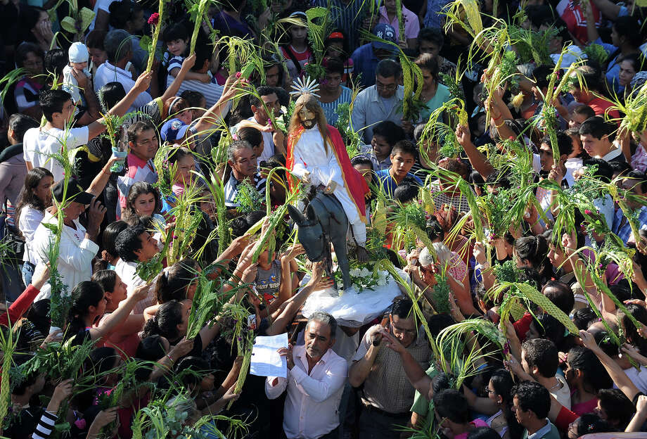Catholic faithfuls waves palm leaves during a Palm Sunday procession in Capiata, 24 km east of Asuncion, on March 24, 2013. For Christians, Palm Sunday marks the beginning of Holy Week, and commemorates Christ's triumphant entry into Jerusalem on the back of a donkey, welcomed by crowds waving palm branches, before his arrest, trial, crucifixion and resurrection. It is traditionally marked by a procession and special mass. Photo: NORBERTO DUARTE, AFP/Getty Images / 2013 AFP
