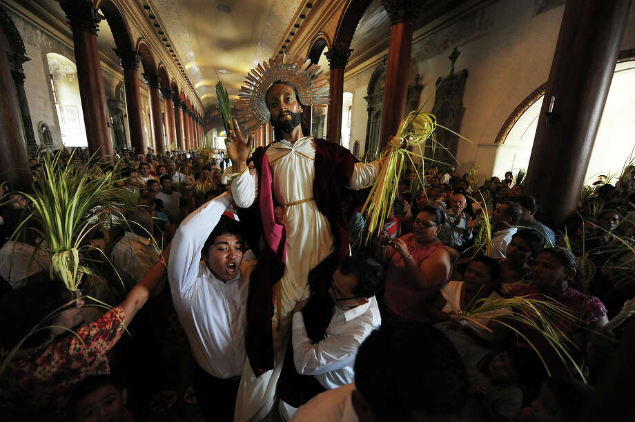 A Catholic faithful participates in a Palm Sunday procession in the town of Suchitoto, 47 km east from San Salvador, on March 24, 2013. Palm Sunday marks the start of the most solemn week is the Roman Catholic calendar, marking the triumphant return of Christ to Jerusalem the week before his death, when a cheering crowd greeted him waving palm leaves. Photo: JOSE CABEZAS, AFP/Getty Images / 2013 AFP