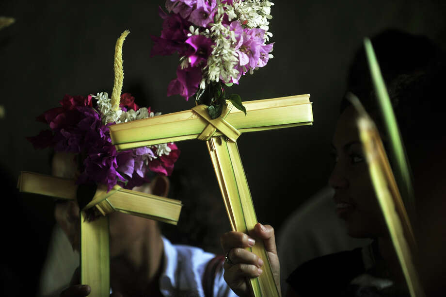 Catholic faithfuls participate in a Palm Sunday procession in Managua, on March 24, 2013. Palm Sunday marks the beginning of Holy Week, and commemorates Christ's triumphant entry into Jerusalem on the back of a donkey, welcomed by crowds waving palm branches, before his arrest, trial, crucifixion and resurrection. It is traditionally marked by a procession and special mass. Photo: HECTOR RETAMAL, AFP/Getty Images / 2013 AFP