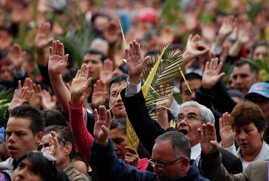 Faithful pray during a Palm Sunday Mass at the Baby Jesus Church in Bogota, Colombia, Sunday March 24, 2013. According to the New Testament, Palm Sunday marks the day Jesus rode into Jerusalem, greeted by cheering crowds bearing palm fronds. For Christians, Palm Sunday marks the start of Holy Week. The week continues with commemorations of Jesus' crucifixion on Good Friday before celebrating his resurrection on Easter the following Sunday. Photo: Fernando Vergara, AP / AP