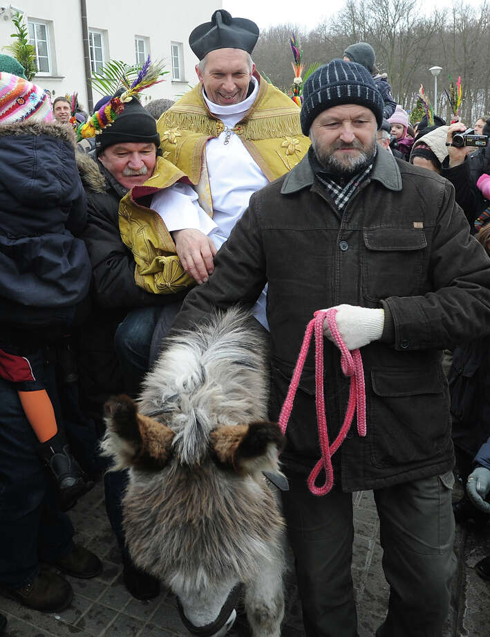 A priest rides a donkey during a Palm Sunday procession in Warsaw, Poland, Sunday, March 24, 2013. Palm Sunday,  the feast commemorating Jesus' triumphal entry on a donkey into Jerusalem, opens the Holy Week which ends with Easter Sunday, the most important Catholic holiday. Photo: Alik Keplicz, AP / AP