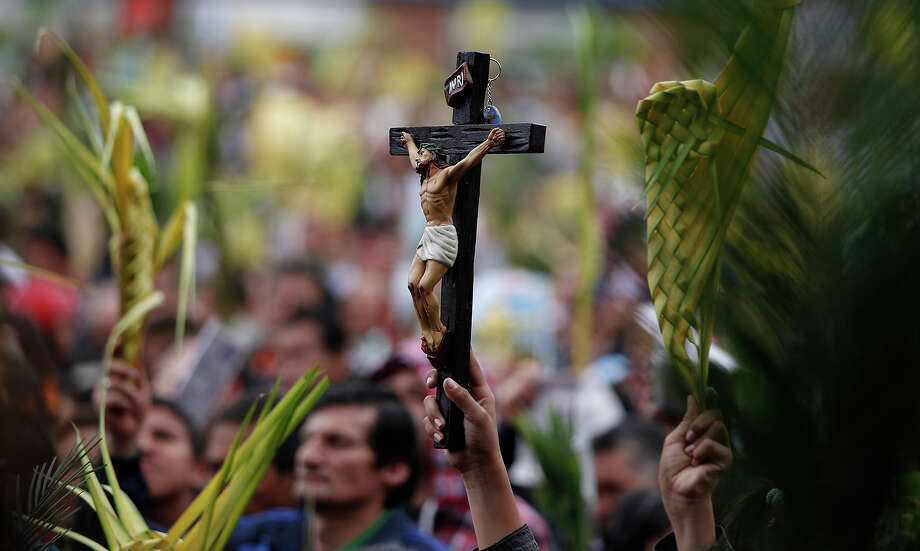 Faithful hold palm fronds and a crucifix during a Palm Sunday Mass at the Baby Jesus Church in Bogota, Colombia, Sunday March 24, 2013. According to the New Testament, Palm Sunday marks the day Jesus rode into Jerusalem, greeted by cheering crowds bearing palm fronds. For Christians, Palm Sunday marks the start of Holy Week. The week continues with commemorations of Jesus' crucifixion on Good Friday before celebrating his resurrection on Easter the following Sunday. Photo: Fernando Vergara, ASSOCIATED PRESS / AP2013