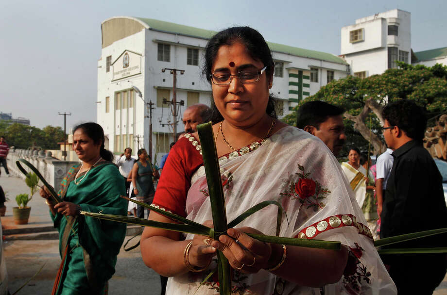 An Indian Catholic woman makes a cross with palm leaves during a Palm Sunday procession at the St. Joseph Cathedral in Hyderabad, India, Sunday, March 24, 2013. Palm Sunday marks the sixth and last Sunday of the Christian Holy month of Lent and the beginning of Holy Week. Photo: Mahesh Kumar A, ASSOCIATED PRESS / AP2013