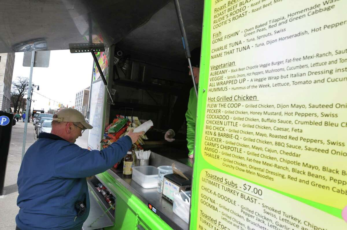 Customer Bill Waller from Clifton Park grabs his lunch at the Healthy Cafe food truck outside the Capitol on Washington Ave. on Monday, March 25, 2013, in Albany, NY. Monday was the first day this season that the food carts and trucks were allowed back at the curb. Kim Comtois, manager of the Healthy Cafe, said that this season they hope to use the smartphone app GrubHub to allow customers to order food in the area around the Capitol and the Healthy Cafe will deliver. (Paul Buckowski / Times Union)
