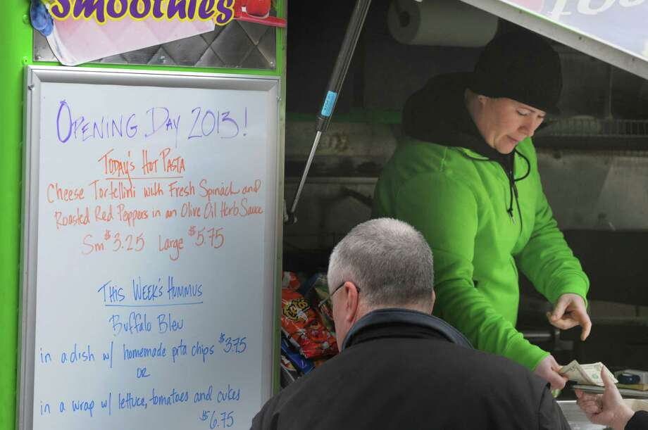 Manager Kim Comtois hands change back to a customer at the Healthy Cafe food truck outside the Capitol on Washington Ave. on Monday, March 25, 2013, in Albany, NY.  Monday was the first day this season that the food carts and trucks were allowed back at the curb.  Kim Comtois, manager of the Healthy Cafe, said that this season they hope to use the smartphone app GrubHub to allow customers to order food in the area around the Capitol and the Healthy Cafe will deliver.   (Paul Buckowski / Times Union) Photo: Paul Buckowski