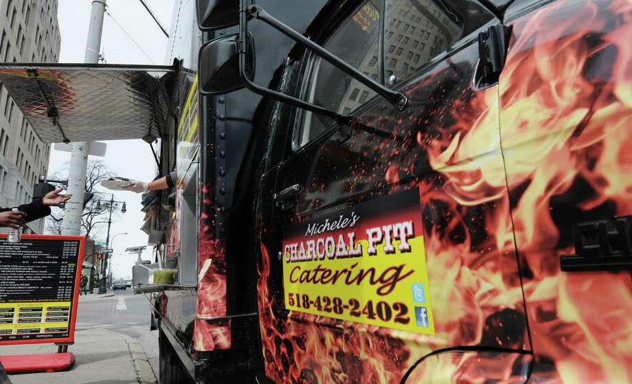 A plate of food is handed out to a customer at Michele's Charcoal Pit food truck outside the Capitol on Washington Ave. on Monday, March 25, 2013, in Albany, NY.  Monday was the first day this season that the food carts and trucks could be back at the curb.  Michele's Charcoal Pit has been around since 1986 and workers said that almost all their prices have stayed the same from last season.  (Paul Buckowski / Times Union) Photo: Paul Buckowski