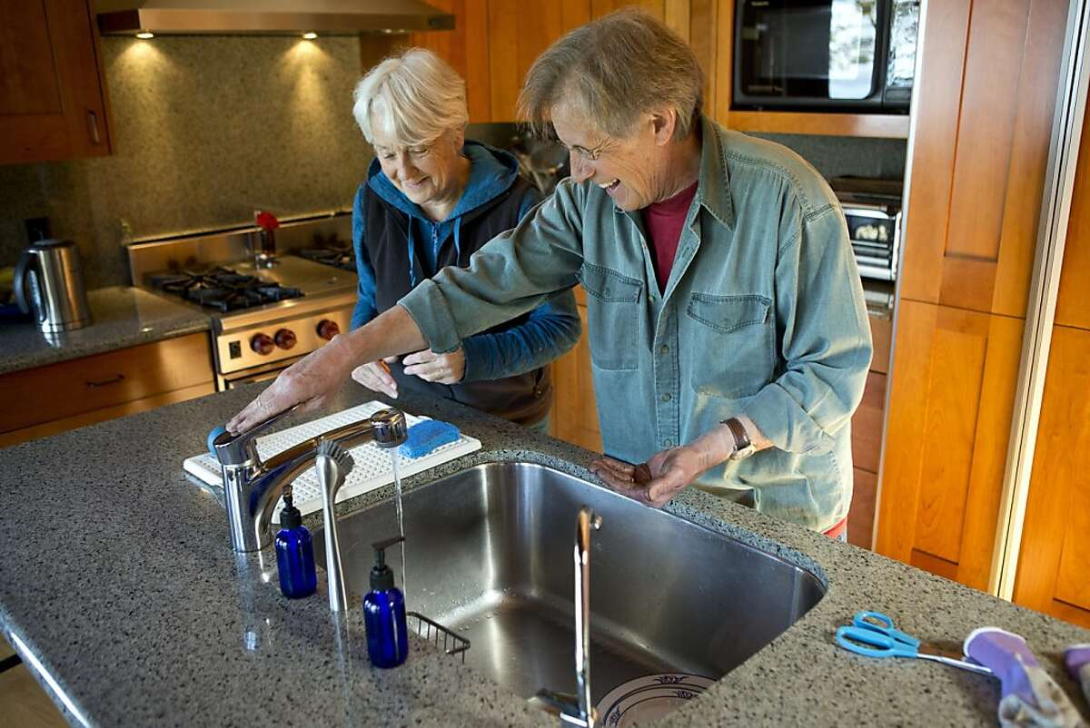 Ashby Village volunteer Angus Dunstan (right) washes his hands with Barbara Blomer after helping her plant flowers in her backyard on Thursday, March 21, 2013 in Berkeley, Calif.
