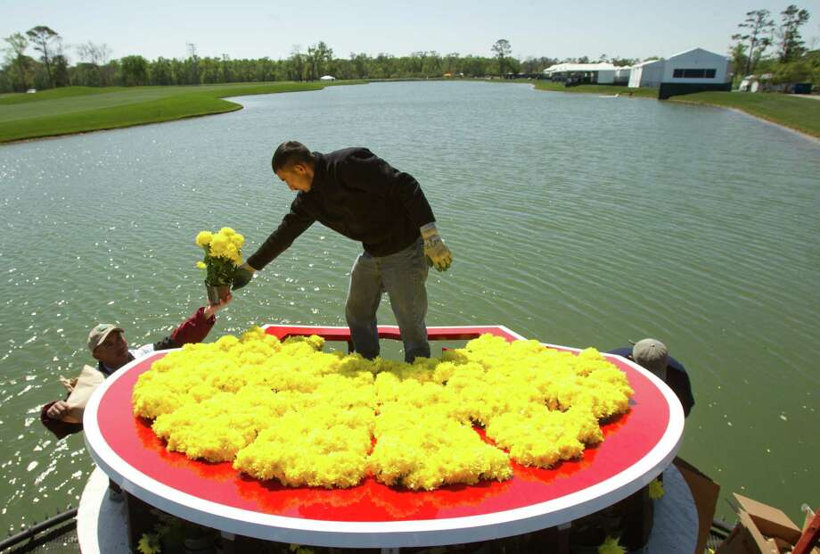 Rodrigo Del Cid, of Landscape Art, puts together the Shell log made of yellow Mums  flowers in preparation for the Shell Houston Open Pro-Am at Redstone Tournament Course Monday, March 25, 2013, in Humble. The opening round for the PGA Tour event is scheduled for Thursday. Photo: Brett Coomer, Houston Chronicle / © 2013 Houston Chronicle