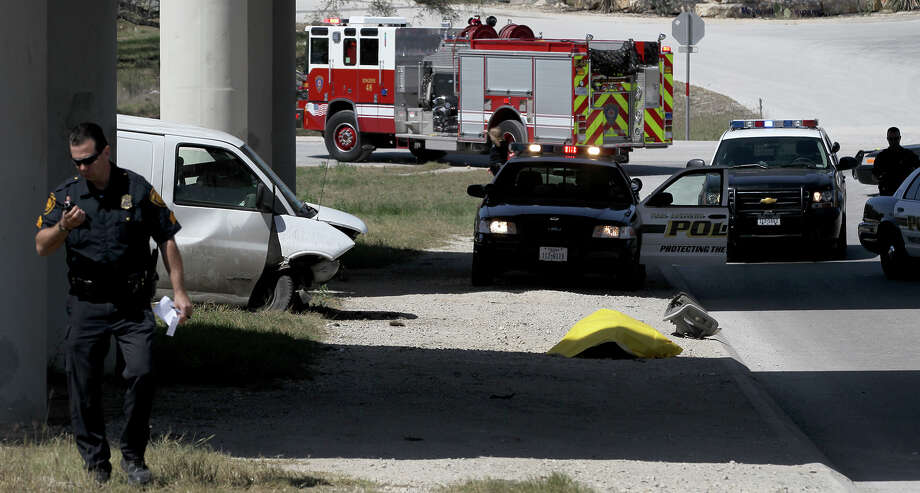 San Antonio police and fire personnel work Monday afternoon March 25, 2013 at O'Connor Road and Loop 1604 where a van crashed off the eastbound lane of 1604 and landed below on O'Connor killing the passenger that was riding in the van. According to San Antonio police sergeant Eddie Rohmer, the van had a blowout on the indside eastbound lane of 1604 and crashed below on O'Connor and the van's passenger attempted to jump out of the passenger door while the van was crashing. The driver was not injured and the passenger died at the scene about 2:30 p.m. . Photo: JOHN DAVENPORT, SAN ANTONIO EXPRESS-NEWS / ©San Antonio Express-News/Photo may be sold to the public