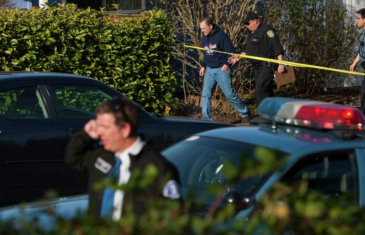 Police lead the suspected driver from the scene of a North Seattle car-pedestrian collision away from the crash site on Monday, March 25, 2013, near Nathan Eckstein Middle School in Seattle.