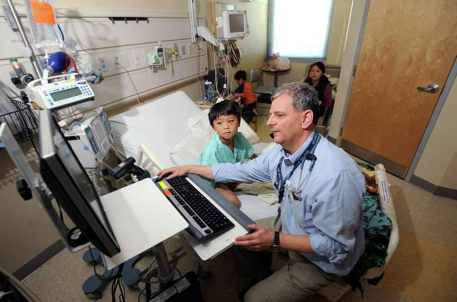 Dr. Jason Snitzer shows Connor Huynh, 7, his medical record at a Kaiser Permanente medical center in Santa Clara, Calif. There are concerns about whether an all-encompassing health care system like Kaiser's can be replicated as the future of health care. Photo: Noah Berger / New York Times