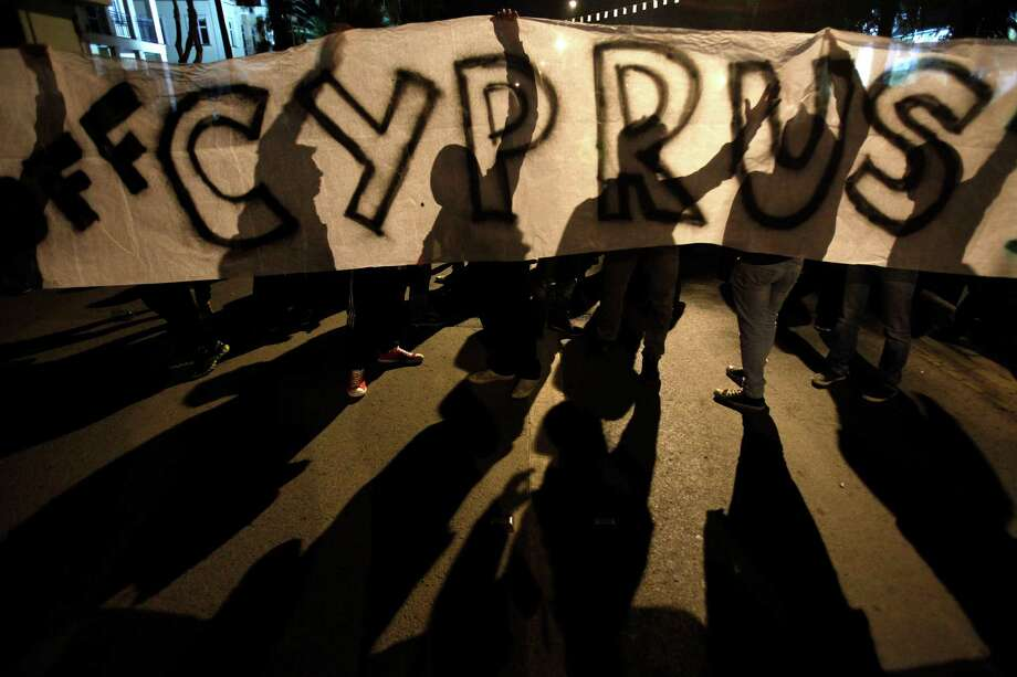 "Protesters hold a banner that reads ""Hands off Cyprus"" during an anti-bailout rally outside European Union house in capital Nicosia, Cyprus, Sunday, March 24, 2013. After failing for a week to find a solution to a crisis that could force their country into bankruptcy, Cypriot politicians turned to the European Union on Sunday in a last-ditch effort to help the island nation forge a viable plan to secure an international bailout. (AP Photo/Petros Karadjias) Photo: Petros Karadjias, STF / AP"