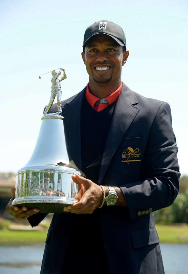 Tiger Woods holds the championship trophy after winning the Arnold Palmer Invitational golf tournament in Orlando, Fla., Monday, March 25, 2013. Woods finished 13-under-par. (AP Photo/Phelan M. Ebenhack) Photo: Phelan M. Ebenhack