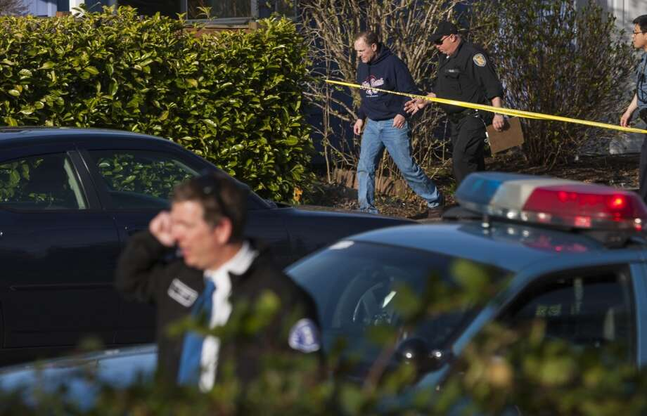 The driver suspected of killing two pedestrians and injuring two others is led away by police. He was arrested shortly after 5 p.m. (Jordan Stead, seattlepi.com)