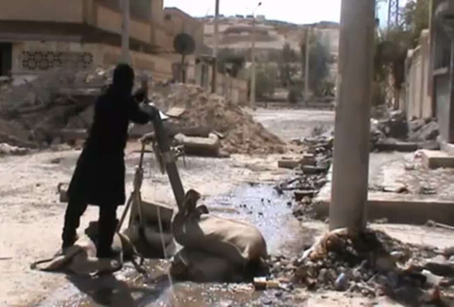 In this Sunday, March 24, 2013 image taken from video obtained from the Ugarit News, which has been authenticated based on its contents and other AP reporting, Free Syrian Army fighters drops a shell into a firing tube, in Damascus countryside, Syria. (AP Photo/Ugarit News via AP video) Photo: Uncredited, HOEP / Ugarit News