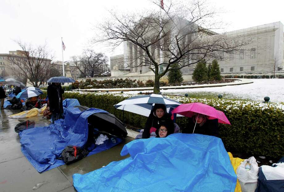 Taylor, Talla and Vincent Carter cover themselves from the snow as they wait in line outside of the Supreme Court in Washington, Monday March, 25, 2013, to watch Tuesday's same-sex marriage hearing before the Supreme Court. (AP Photo/Jose Luis Magana) Photo: Jose Luis Magana