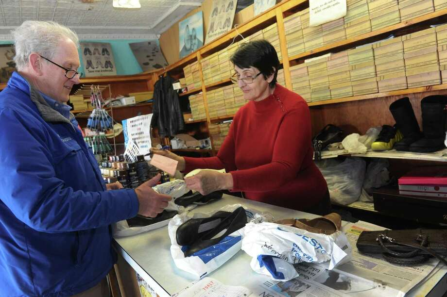 Anna Conte, right, hands Bob Keplinger of Schenectady his repaired shoes at Colonie Shoe Repair on Tuesday March 20, 2013 in Colonie, N.Y. (Michael P. Farrell/Times Union) Photo: Michael P. Farrell