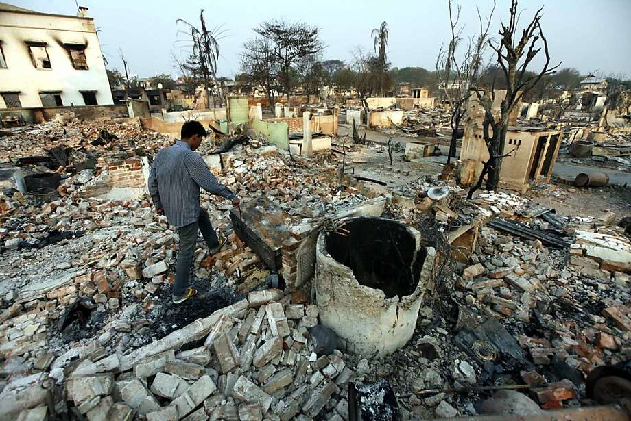 A man walks among debris of buildings destroyed during ethnic unrest between Buddhists and Muslim in Meikhtila, about 550 kilometers (340 miles) north of Yangon, Myanmar, Monday, March 25, 2013. Sectarian clashes between Buddhists and Muslims in Meikhtila spread to at least two other towns in the country's heartland over the weekend, undermining government efforts to quash an eruption of violence that has killed dozens of people and displaced 10,000 more. On Sunday, Vijay Nambiar, the U.N. secretary-general's special adviser on Myanmar, toured Meikhtila, where soldiers were able to impose order after several days of anarchy, and called on the government to punish those responsible. (AP Photo/Khin Maung Win) Photo: Khin Maung Win, Associated Press