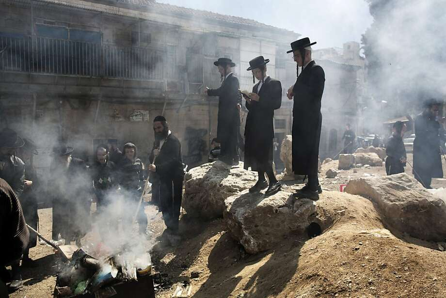 Ultra-Orthodox Jews pray as they burn leavened items in a final preparation before the start at sundown of the Jewish Pesach (Passover) holiday, on March 25, 2013 in Jerusalem. Religious Jews worldwide eat matzoh during the eight-day Pesach holiday that commemorates the Israelis' exodus from Egypt some 3,500 years ago and their ancestors' plight by refraining from eating leavened food products. MENAHEM KAHANA/AFP/Getty Images Photo: Menahem Kahana, AFP/Getty Images