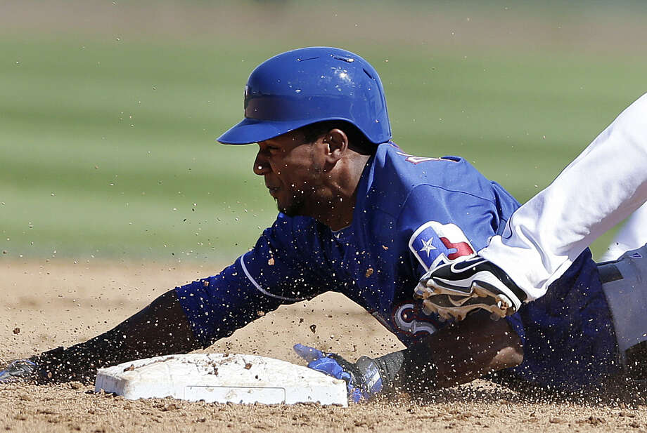 Julio Borbon of the Rangers slides safely into second base with a steal in the sixth inning. Photo: Gregory Bull / Associated Press