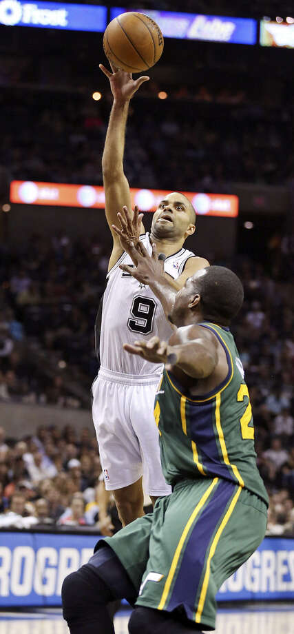 Spurs point guard Tony Parker shoots one of his trademark floaters over Utah's Paul Millsap on Friday in his return from a sprained ankle. Photo: Edward A. Ornelas / San Antonio Express-News