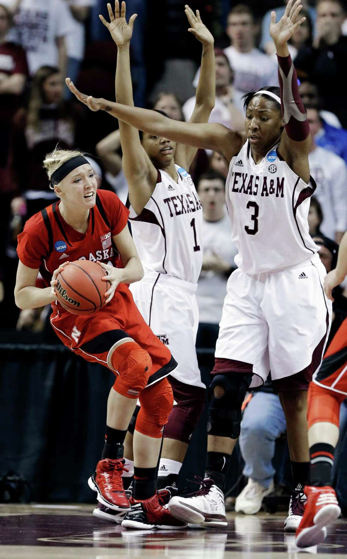 Nebraska's Emily Cady, left, is pressured by Texas A&M's Courtney Williams (1) and Kelsey Bone (3) during a second-round game in the NCAA women's college basketball tournament in College Station, Texas, Monday, March 25, 2013.