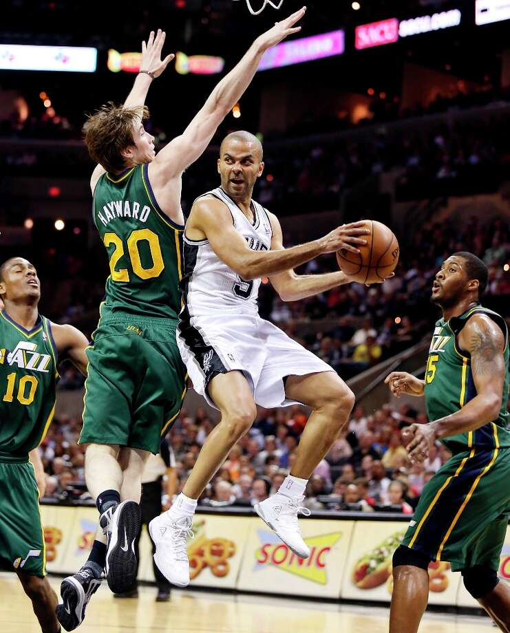 The Spurs' Tony Parker looks to pass between Utah Jazz's Alec Burks (from left), Gordon Hayward and Derrick Favors during first half action Friday, March 22, 2013 at the AT&T Center. Photo: Edward A. Ornelas, San Antonio Express-News / © 2013 San Antonio Express-News