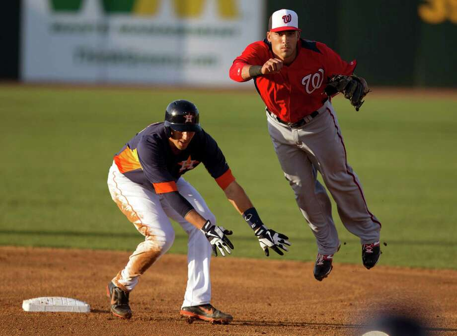 Nationals shortstop Ian Desmond, right, dodges the Astros' Jason Castro while turning a double play in the second inning Monday night. Photo: Evan Vucci, STF / AP