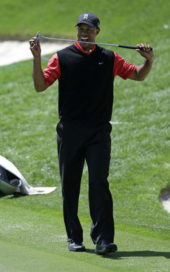 Tiger Woods bites his club after a rare missed putt at the Arnold Palmer Invitational. Photo: John Raoux / Associated Press