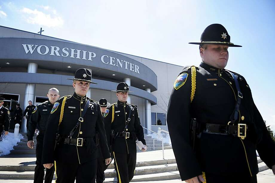 Colorado police officers leave New Life Church in Colorado Springs Colo., after celebrating the life of Colorado prisons chief Tom Clements during a memorial service Monday, March 25, 2013 after he was gunned down as he answered the door to his home last week. (AP Photo/The Gazette, Michael Ciaglo) Photo: Michael Ciaglo, Associated Press