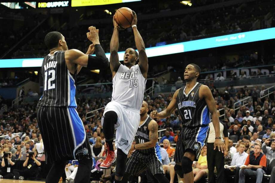 Mario Chalmers shoots over Tobias Harris in Miami's 27th straight victory, a runaway against the Magic on Monday in Orlando. Chalmers scored 17 points. Photo: Gary Bogdon / Getty Images