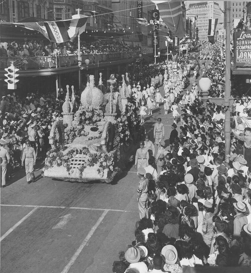 Battle of Flowers 1948: A portion of the parade, which wound through city streets more than two hours, passes the Gunter Hotel on Houston Street, going west. Above, several floats pass majestically, flanked by military escorts and followed by prancing high school drum majorettes. Photo: San Antonio Express-News File Photo