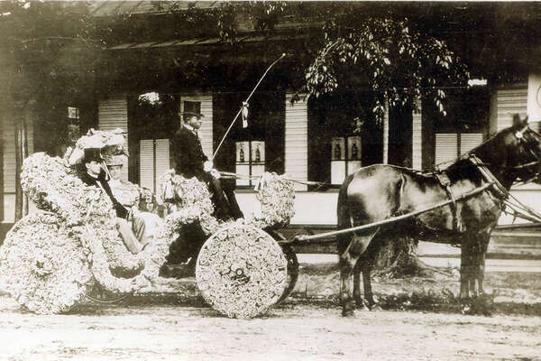 Battle of Flowers 1906: Col. and Mrs. Frank H. Bushick Sr. ride in a flower-adorned carriage with driver for the parade. Frank Bushick was president of the Battle of Flowers Association at the time, and managing editor of the San Antonio Express. This picture given to Jean Dugat by her uncle, Gentry Dugat, in 1955.