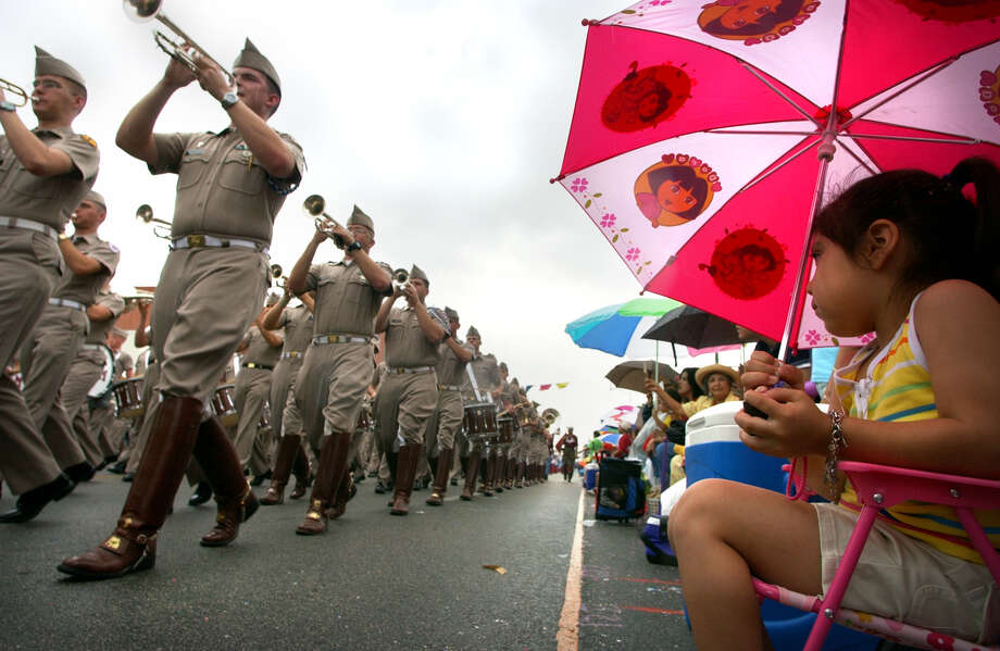 Battle of Flowers 2004: Gabriela Ramirez, 3, sits under her umbrella as the Texas A&M Aggie Band marches down Broadway. Photo: Bob Owen / San Antonio Express-News / SAN ANTONIO EXPRESS-NEWS